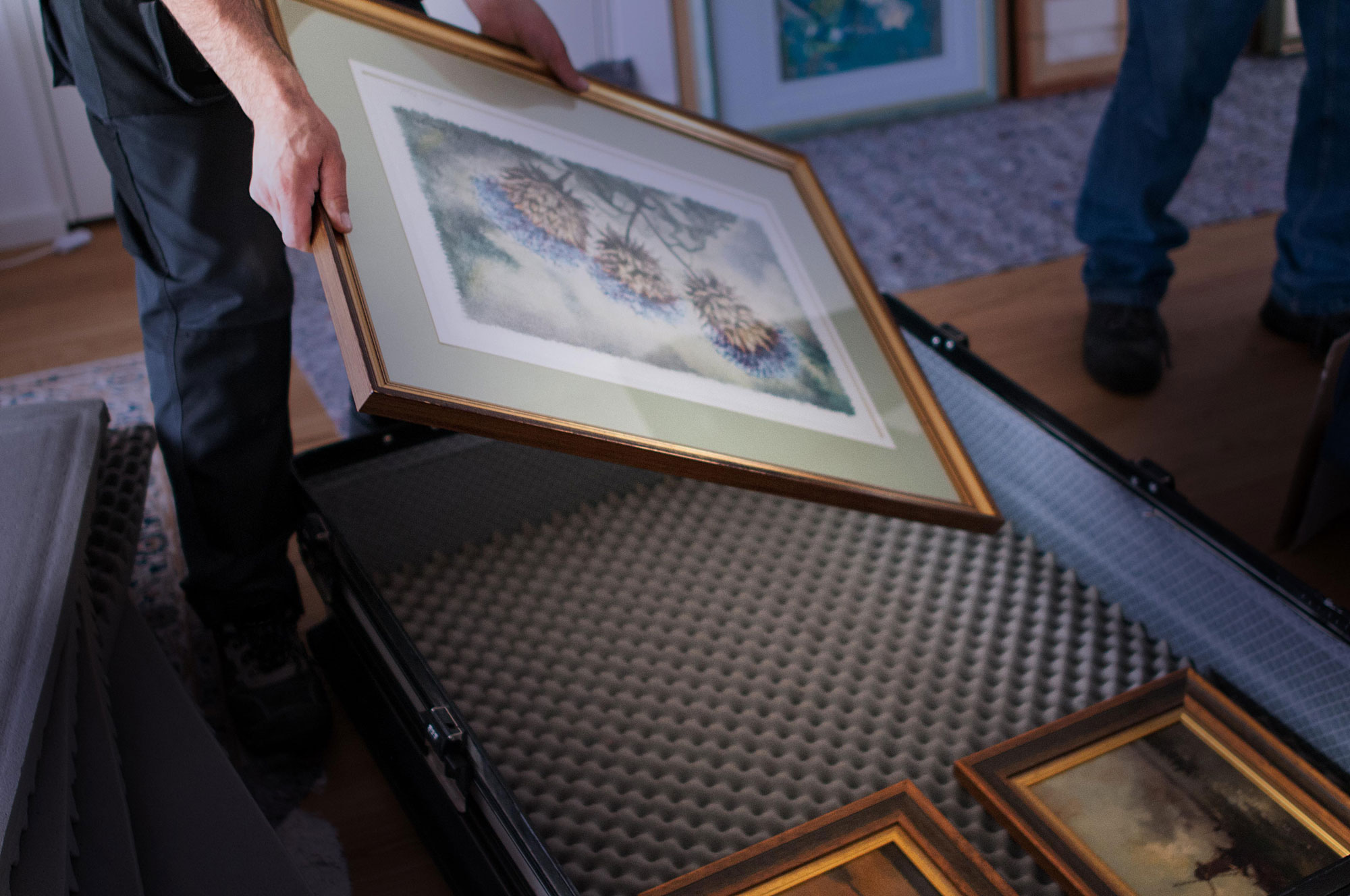 Bild von einem Gemälde, dass sorgsam in einem Bilderkoffer verstaut wird.